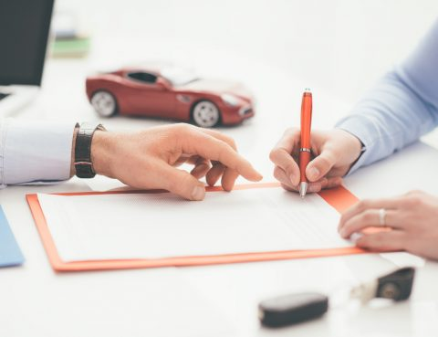 Driver signing a car insurance